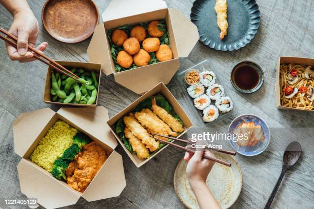 sharing assorted takeaway meal at home - take away food stock pictures, royalty-free photos & images