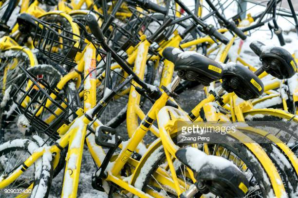 Sharing bikes are scattered and covered with snow in a mess at roadside The supply of sharing bikes has been saturated and many Chinese cities have...