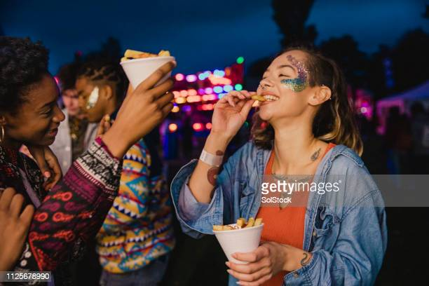 sharing chips at a festival - carnival stock pictures, royalty-free photos & images