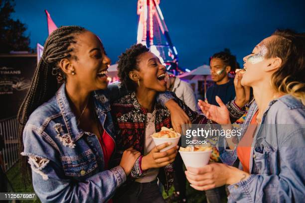 sharing chips at a funfair - french fries stock pictures, royalty-free photos & images