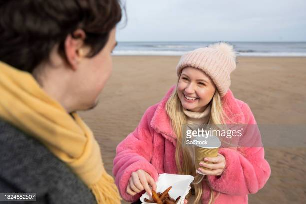 sharing chips at the beach - headwear stock pictures, royalty-free photos & images