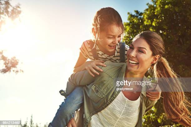sharing good times on a golden afternoon - piggyback stock pictures, royalty-free photos & images