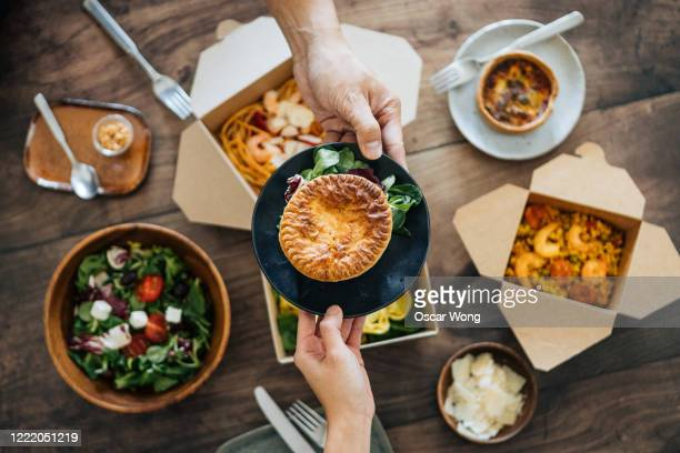 sharing takeaway meal on dining table - giving stock pictures, royalty-free photos & images