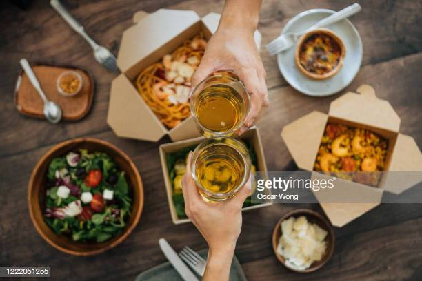 sharing takeaway meal on dining table - human hand stock pictures, royalty-free photos & images