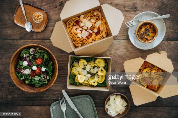 sharing takeaway meal on dining table - elevated view stock pictures, royalty-free photos & images