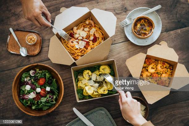sharing takeaway meal on dining table - take away food stock pictures, royalty-free photos & images