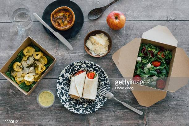 sharing takeaway vegetarian meal on dining table - gourmet stock pictures, royalty-free photos & images