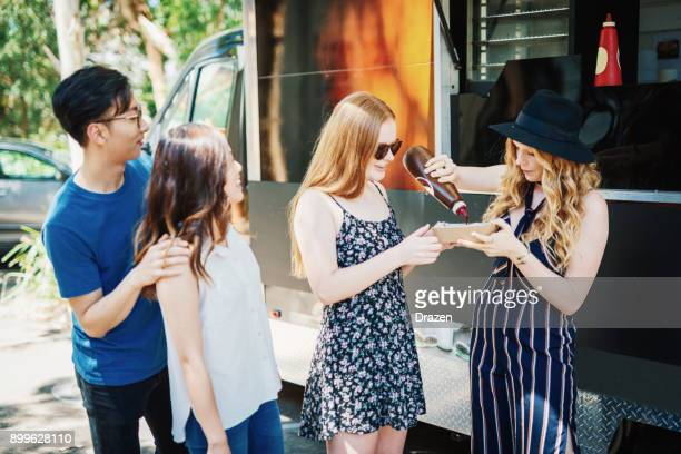 sharing tasty snack near the food truck - korean teen stock pictures, royalty-free photos & images