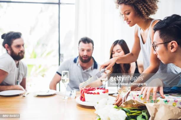 Sharing the birthday cake between friends.