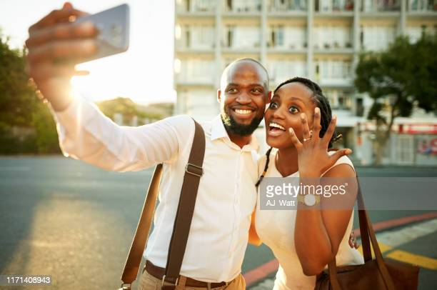 sharing their news with friends - black women engagement rings stock pictures, royalty-free photos & images