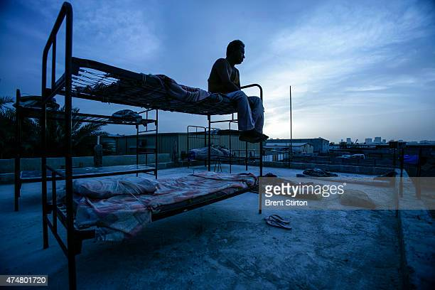 An abandoned migrant labourer sits on a rooftop in a squallid makeshift camp in Sharjah the Emirate next to Dubai This man and another 300 workers...