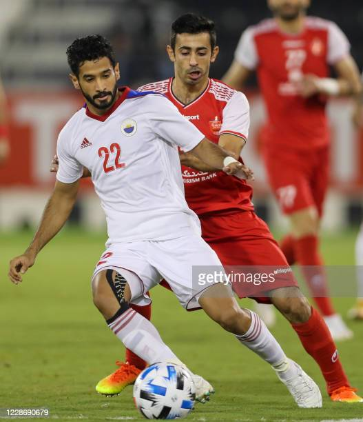 Sharjah's defender Marcos Meloni is marked by a Persepolis player during the AFC Champions League group C match between Iran's Persepolis and UAE's...