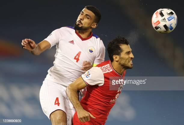 Sharjah's defender Shahin Abdulrahman vies for the header with Persepolis player during the AFC Champions League group C match between Iran's...