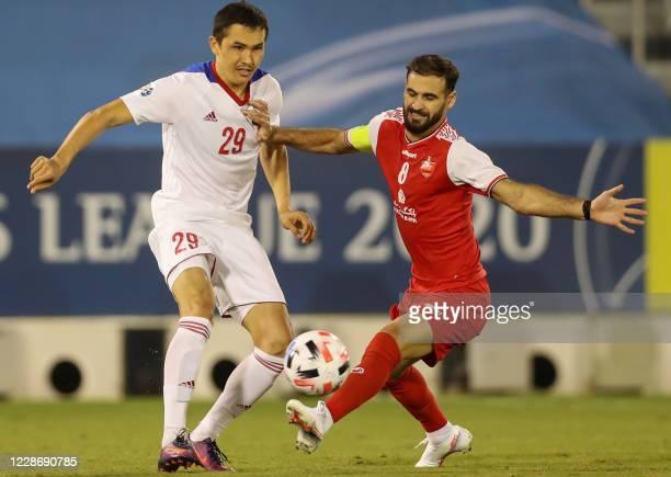 Sharjah's midfielder Otabek Shukurov is marked by Persepolis' midfielder Ahmad Nourollahi during the AFC Champions League group C match between...