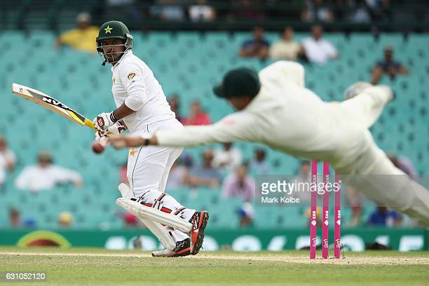 Sharjeel Khan of Pakistan watches as an edge flies past a diving Usman Khawaja of Australia during day four of the Third Test match between Australia...