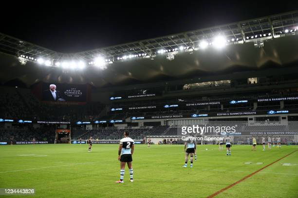 Sharks and Tigers players pay their respect during a minutes silence for the late Arthur Summons during the round three NRL match between the...