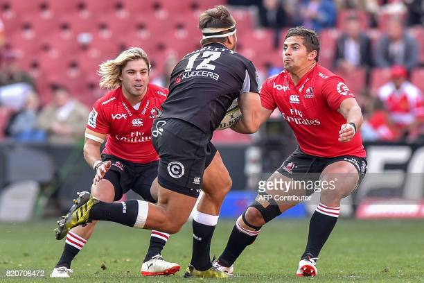 Sharks' Andre Esterhuizen tries to escape a tackle from Lions' Faf De Klerk and Rohan Janse van Rensburg during the Super Rugby quarterfinal match...