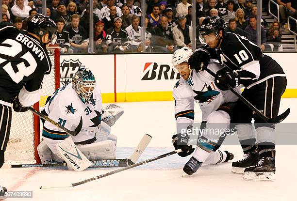 LOS ANGELES CA TUESDAY APRIL 22 2014 Sharks defenseman Brad Stuart knocks the puck away from Kings center Mike Richards who is trying to catch up...