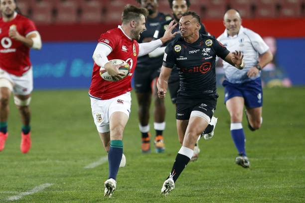 Sharks' fly-half Curwin Bosch (R) chases British and Irish Lions' centre Elliot Daly (L) during a rugby union tour match between the Sharks against the British and Irish Lions at the Ellis Park stadium in Johannesburg on July 7, 2021. (Photo by Phill Magakoe / AFP) (Photo by PHILL MAGAKOE/AFP via Getty Images)