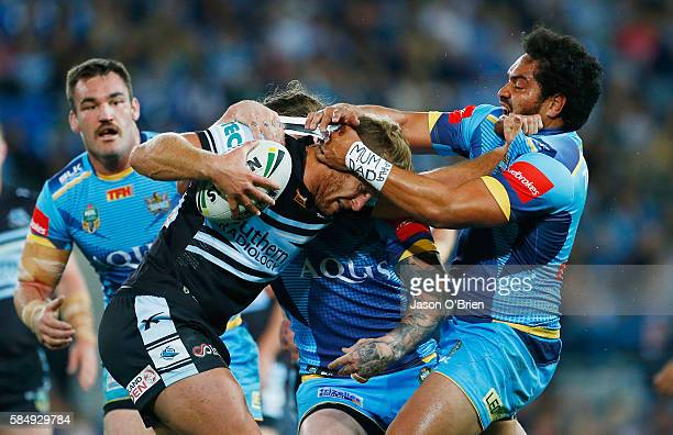Shark's Matt Prior is tackled by the Titans defence during the round 21 NRL match between the Gold Coast Titans and the Cronulla Sharks at Cbus Super...