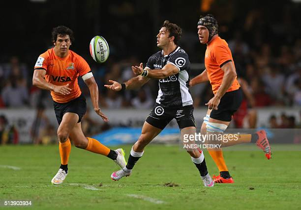 Sharks' South African Paul Jordaan passes the ball in front of Jaguares' Matias Alemanno and Matias Moroni during the Super Rugby match between...