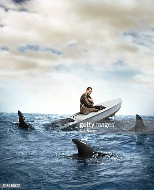 sharks surrounding man sitting in sinking boat - sinking stock pictures, royalty-free photos & images