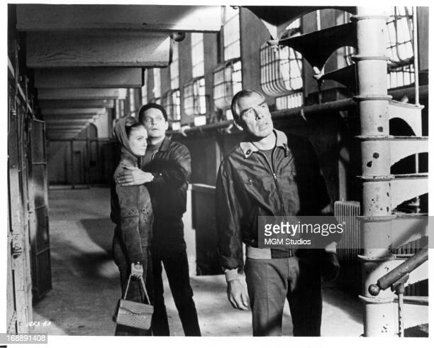 Sharon Acker is held by John Vernon as Lee Marvin looks up a staircase in a scene from the film 'Point Blank' 1967