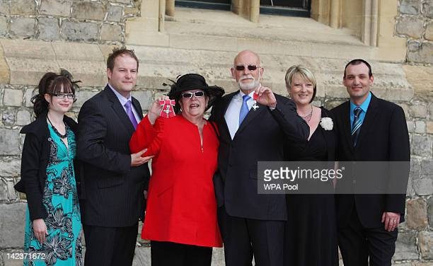 Sharon and Clive Cumming pose with their MBEs awarded by Queen Elizabeth II for services to Children and Family next to members of their family...