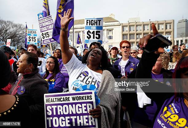 Sharon Brown of Dorchester center throws her hand up during a rally against income inequality and to call for higher wages in key Mass industries in...