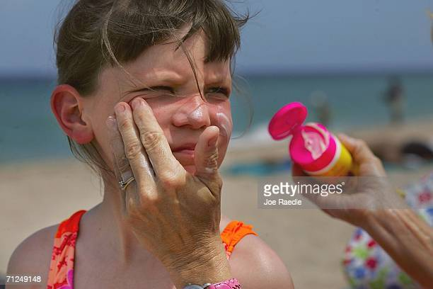 Sharon Doyle puts sunscreen on the face of 9yearold Savannah Stidham as they visit the beach June 20 2006 in Fort Lauderdale Florida Recent studies...