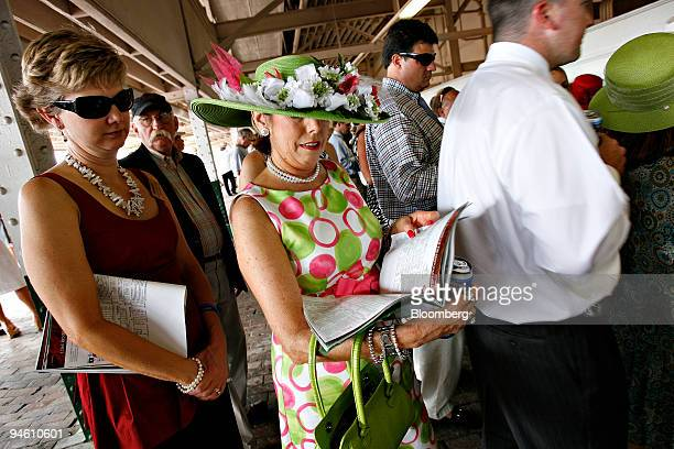 Sharon Kirchner of Louisville looks over the days racing program as she waits in line to place a bet on the Kentucky Derby for her mother at...