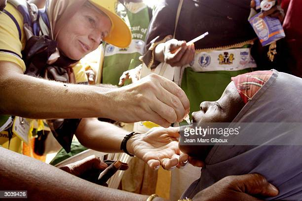 """Sharon McKeown, a Rotarian from Canada, immunizes a Nigerian girl during the official """"flag-off ceremony"""" for the National Immunization Days November..."""