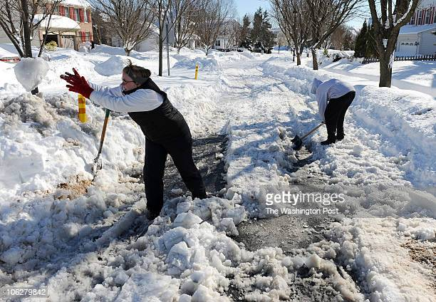 Sharon Neall tosses a big chunk of ice while neighbor Claire Spencer digs out the intersection of Pearl and Price roads They said the snow plow got...
