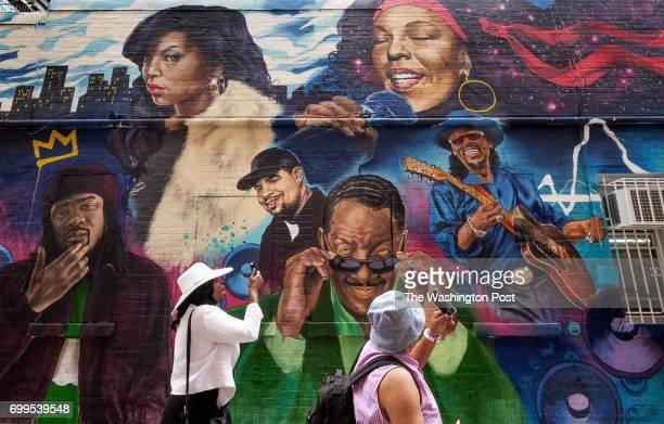 Sharon Parker of Calvert County MD and other visitors photograph a mural created by Aniekan Udofia on a wall at Ben's Chili Bowl in Washington DC on...