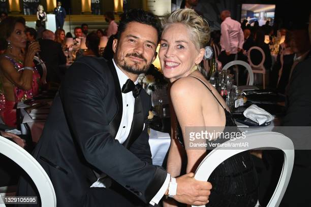 Sharon Stone and Orlando Bloom attend the amfAR Cannes Gala 2021 at Villa Eilenroc on July 16, 2021 in Cap d'Antibes, France.