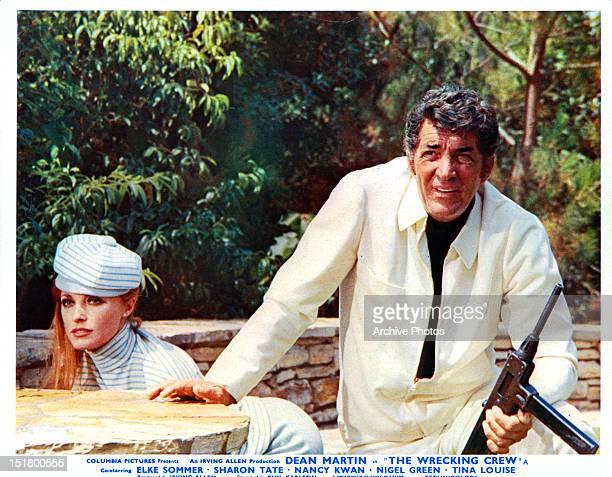Sharon Tate kneeling beside gun wielding Dean Martin in a scene from the film 'The Wrecking Crew', 1968.