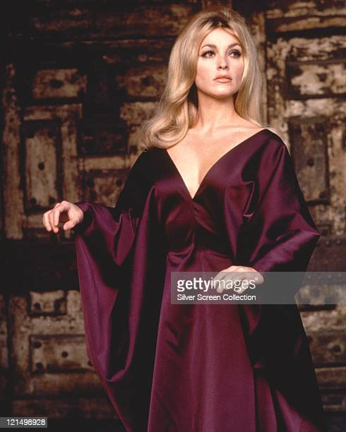 Sharon Tate US actress wearing a purple evening gown with a plunging neckline circa 1965