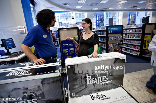 Sharon Tishco talks to employee Bonafide Rojas as she prepares to purchase Viacom Inc's The Beatles Rock Band for a Nintendo Wii at a Best Buy store...