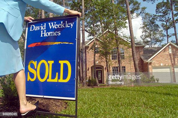Sharon Williams a sales consultant for David Weekley Homes puts in a sold sign in front of a new construction home in The Woodlands Texas Tuesday May...