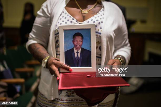 Sharonda Rhodes holds a cap and framed photo of her son Markel T Scott Excel Academy senior who was killed earlier this year during the graduation...