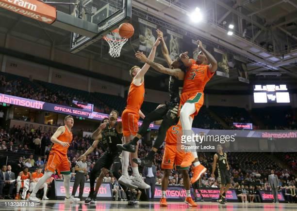 Sharone Wright Jr #2 of the Wake Forest Demon Deacons battles for a loose ball against teammates Sam Waardenburg and Anthony Lawrence II of the Miami...