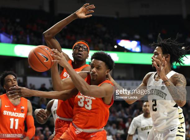 Sharone Wright Jr #2 of the Wake Forest Demon Deacons battles for a loose ball against teamamtes Paschal Chukwu and Elijah Hughes of the Syracuse...