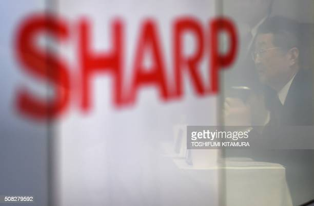Sharp chairman and CEO Kozo Takahashi is reflected on a video monitor while answering questions during a press conference on the company's third...