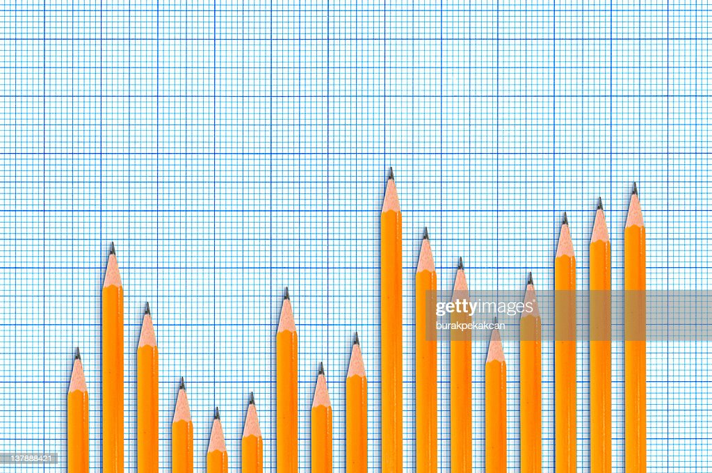 Sharpened pencils forming bar chart on blue graph background : Stockfoto