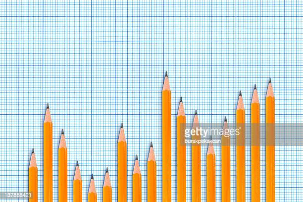Sharpened pencils forming bar chart on blue graph background