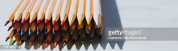sharpened wooden colouring pencils on a white surface with the tips facing the camera - obsessive compulsive disorder stock pictures, royalty-free photos & images