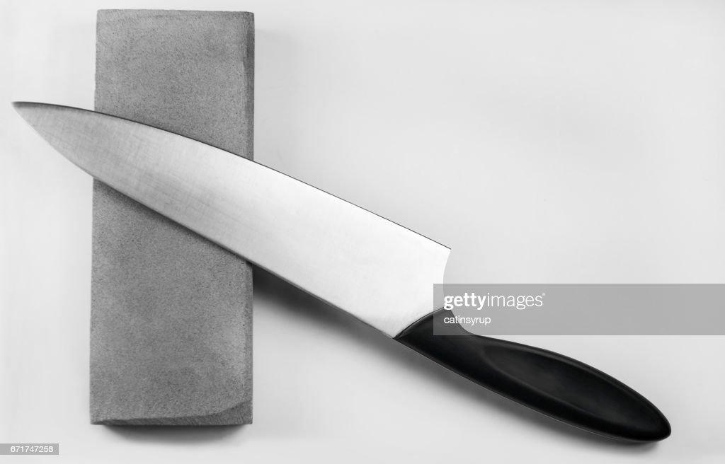 Sharpening a knife on a whetstone, isolated on white background : Stock Photo
