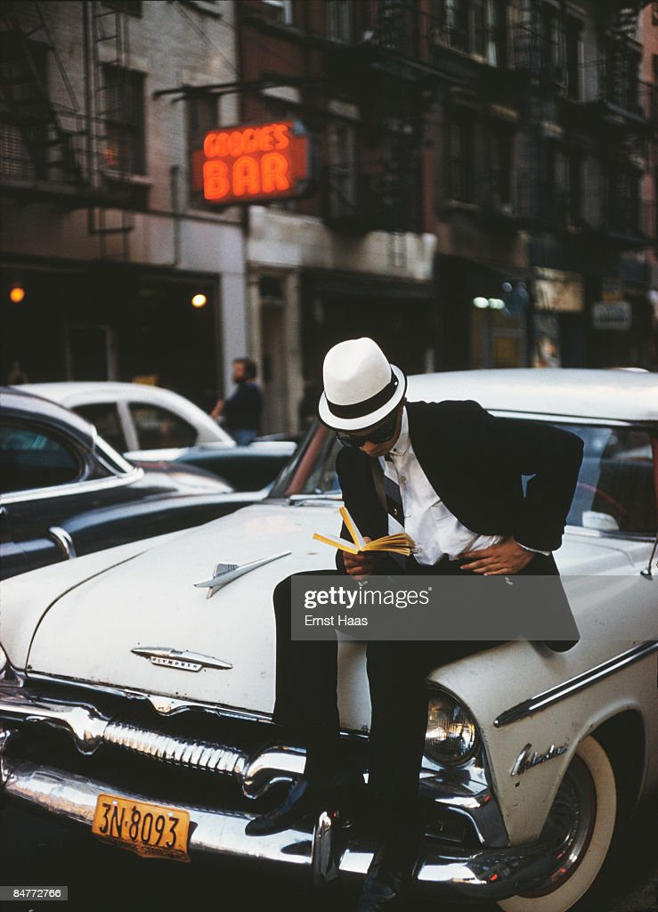A sharply-dressed young man sitting on a Plymouth car and reading a book, New York City, June 1962.