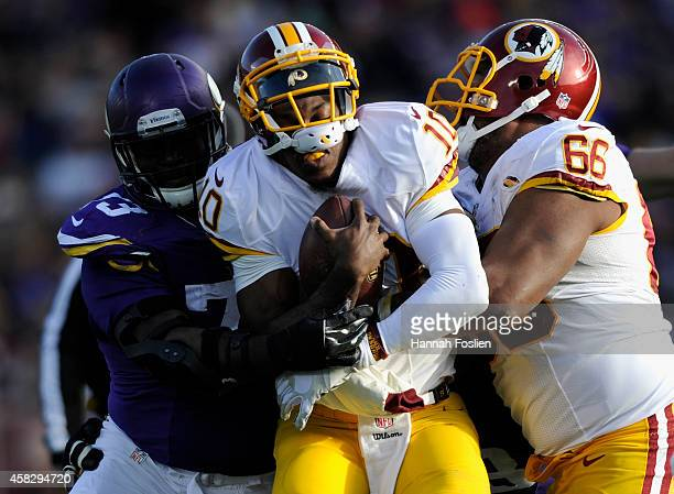 Sharrif Floyd of the Minnesota Vikings stops the progress of Robert Griffin III of the Washington Redskins during the fourth quarter of the game on...