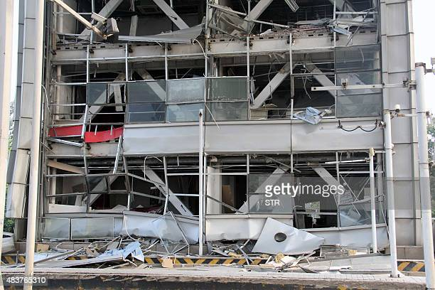 Shattered building windows are seen near the site of a series of explosions in Tianjin on August 13 2015 A series of enormous explosions at an...